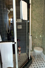 A neo-angle walk-in glass shower is a touch of modern luxury tucked away in this private bath.
