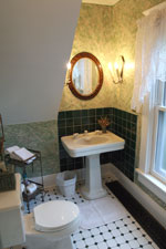A private bath nestles under the back third-floor stairs, with a view of the carriage house from the window.