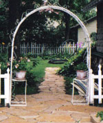 "A stone path leads through an arch  to the ""secret garden"" behind the carriage house"