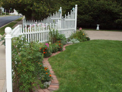 A dream garden welcome - the entrance to the driveway is surrounded with flowers along the white picket fence.