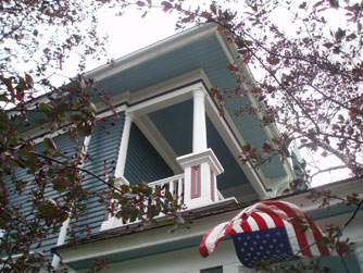 The balcony soars above the front porch, where a flag waves in a strong breeze.